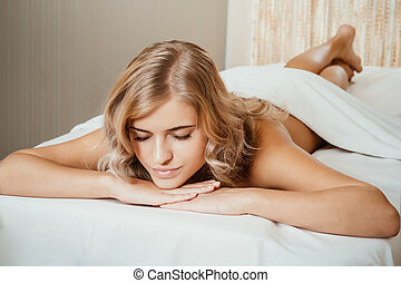 Beautiful young woman in spa relaxing on table waiting for massage