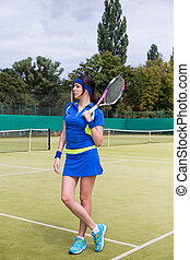 Beautiful young woman in sports clothing holding tennis racket on her shoulder