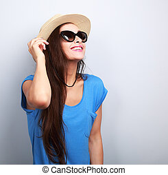 Beautiful young woman in straw hat and fashion sun glasses looking up on empty copy space