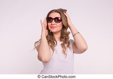 Beautiful young woman in stylish sunglasses over white background