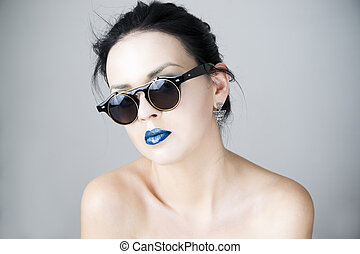 Beautiful young woman in sunglasses on gray background