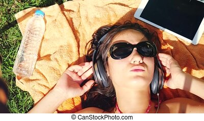 Beautiful young woman in sunglasses lying on the grass, listening to music. 3840x2160