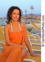 beautiful young woman in swimsuit and pair sitting on yellow chaise lounge in evening on beach