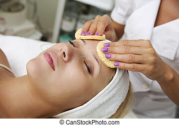 Beautiful young woman in the cosmetic table