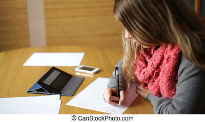 beautiful young woman in the Office writes with pen