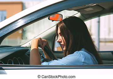 Beautiful young woman in the silver car