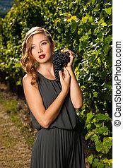 Beautiful young woman in vineyard holding a grape