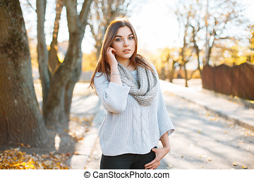 Beautiful young woman in vintage knitted sweater on the background of autumn park