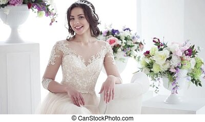 Beautiful young woman in wedding dress. Charming brunette bride sits among the flowers in the Bridal salon