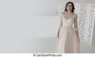 Beautiful young woman in wedding dress. Charming brunette bride.