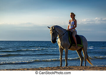beautiful young woman in white dress by the sea with horse