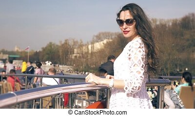 Beautiful young woman in white dress standing on the deck of a river tour boat passing famous Gorky park in Moscow. Slow motion video
