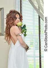 Beautiful young woman in white dress with flower