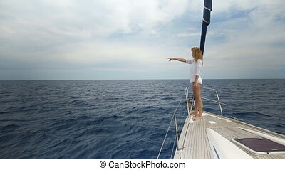 Beautiful young woman in white on the bow of yacht