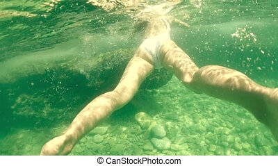 Beautiful young woman in white swimsuit bathing in the sea, underwater shot