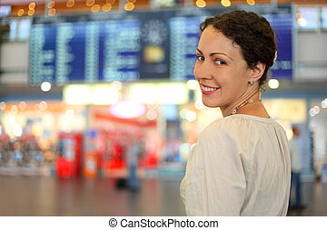 beautiful young woman in white wear in hall of airport, she smiles