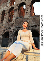 beautiful young woman in white wear sitting near Colosseum at summer day