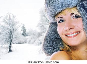 Beautiful young woman in winter fur-cap