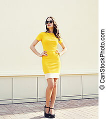 Beautiful young woman in yellow dress and black sunglasses posing outdoors, street fashion