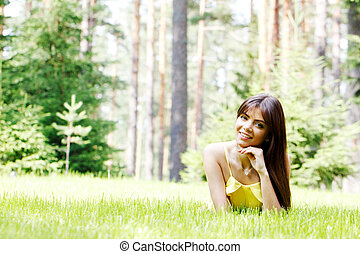young woman in yellow dress lying on grass