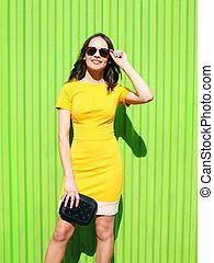Beautiful young woman in yellow dress with black handbag clutch over green wall, street fashion