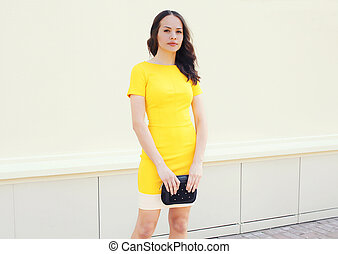 Beautiful young woman in yellow dress with black handbag clutch over white background