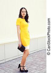 Beautiful young woman in yellow dress with black handbag clutch posing outdoors, street fashion
