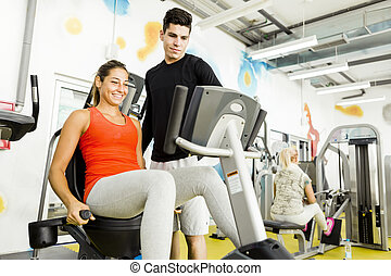 Beautiful young woman instructed by a handsome man in a gym