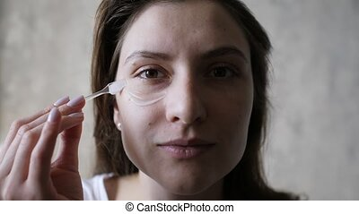 Beautiful young woman is applying a transparent moisturizer against wrinkles on her face. Facial care, natural skin, cosmetics 4k slowmo
