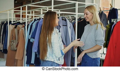 Beautiful young woman is choosing coat in shop and meeting female friend. Girls are happy to see each other, they are hugging, laughing and chatting.