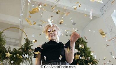 Beautiful young woman is dancing among golden confetti....