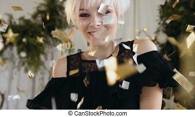 Beautiful young woman is dancing among golden confetti,...