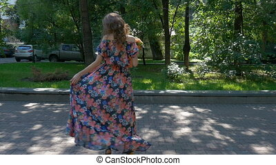 Beautiful young woman is dancing in a park with a bouquet of flowers.