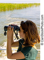 Beautiful young woman is looking through binoculars from the deck of the boat