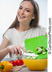 Beautiful young woman is making tasty salad