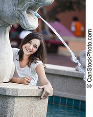 beautiful young woman is playing with fountain