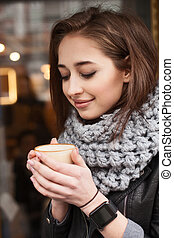 Beautiful young woman is relaxing with coffee