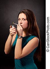 Beautiful young woman is smoking cigarette