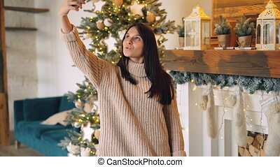 Beautiful young woman is taking selfie with smartphone on Christmas standing near decorated fireplace mantel and New Year tree. Holiday and photo concept.