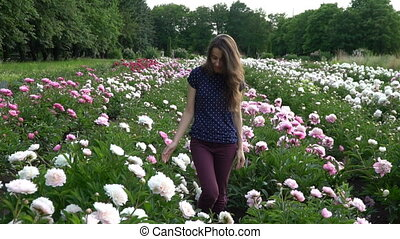 Beautiful young woman is walking in the summer field of peonies