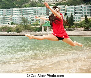 Beautiful young woman jumping in the sea