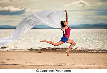 Beautiful young woman jumping on the beach with a white tissue
