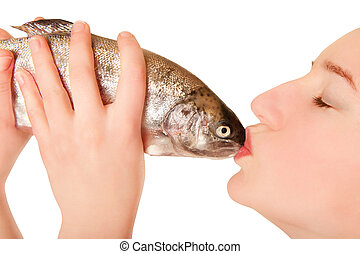 Beautiful young woman kissing a fish