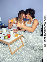 Beautiful young woman kissing to man in bed breakfast