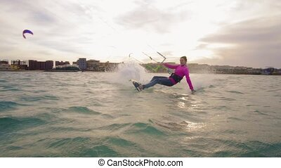Beautiful young woman kiteboarding at sunset in slow motion,...