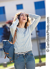 beautiful young woman laughing and talking on phone while walking