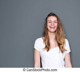 Close up portrait of a beautiful young woman laughing on fray background