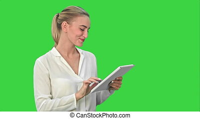 Beautiful young woman laughing while looking at digital tablet on a Green Screen, Chroma Key.