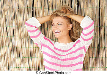 Beautiful young woman laughing with hands in hair