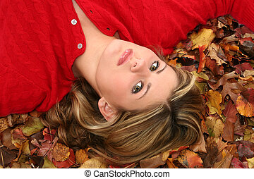 Beautiful Young Woman Laying in Leaves